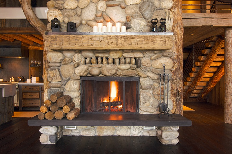 Indoor stone fire place inside log cabin home