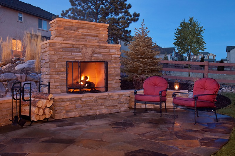 Outdoor stone fireplace with two red chairs