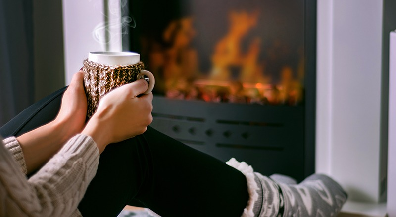 Lady holding coffee mug with in front of fire place
