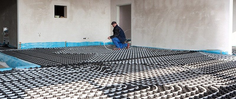 Male in black jacket Installing in-floor heating