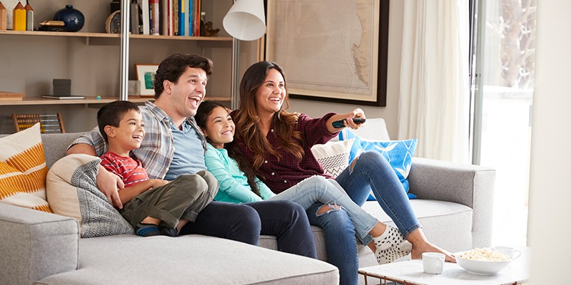 Husband and wife watching TV on couch with son and daughter